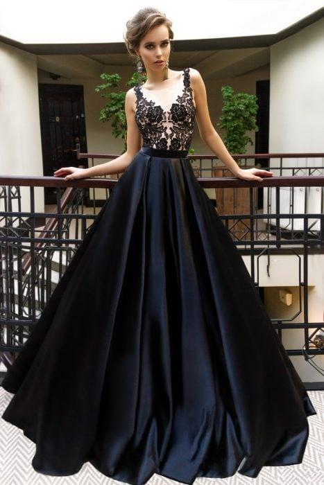 Chica usando un vestido de color negro con escote y pecho de encaje