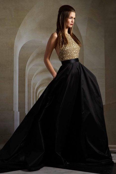 Chica usando un vestido de color negro con dorado