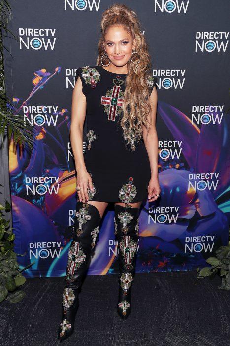 Jennifer Lopez usando unas botas que combinan con su vestido