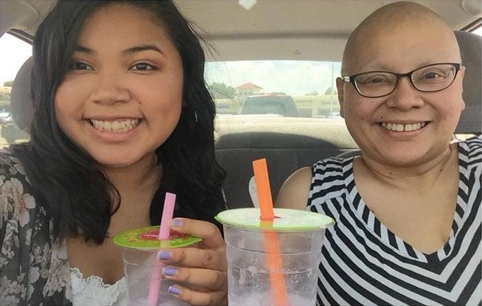 Chica junto a su madre disfrutando de una bebida mientras se toman una foto