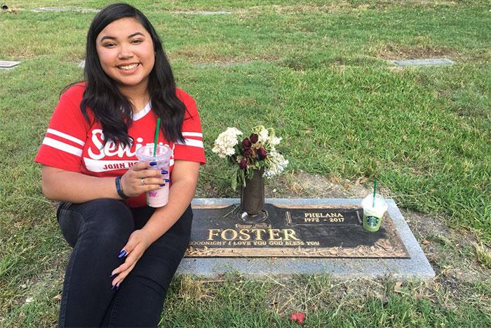 Chica tomandose una fotografía junto a la tumba de su madre