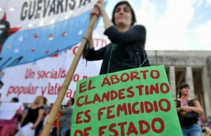 mujer con bandera y pancarta aborto