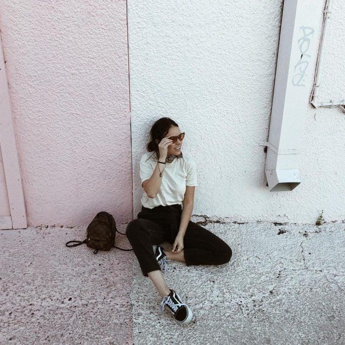 mujer sentada en el suelo en la pared