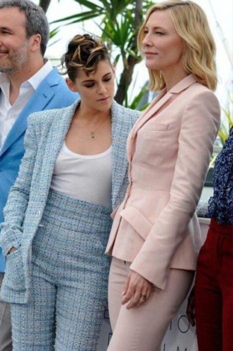 mujer con saco y pantalon rosa pastel y mujer con traje azul