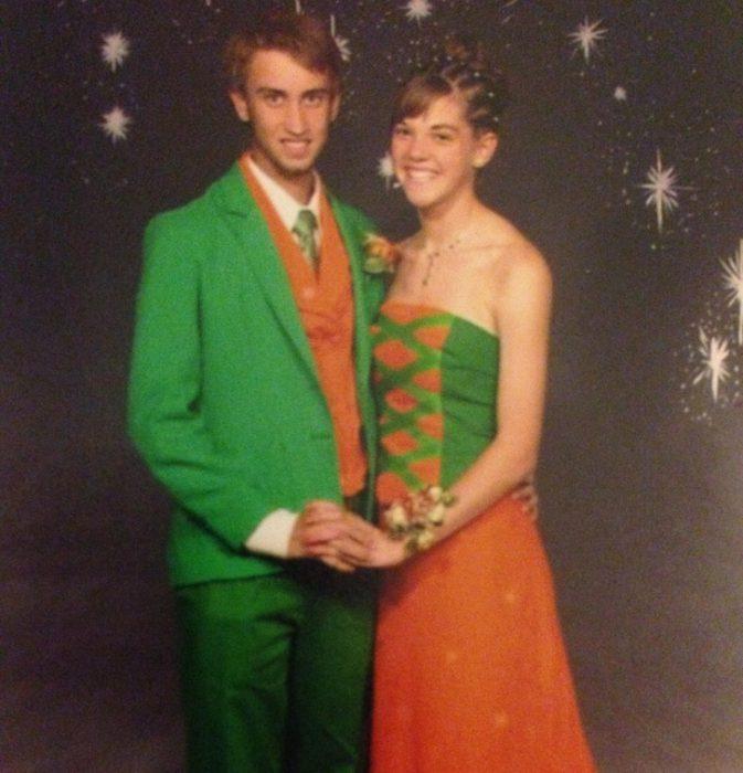 Chico usando un traje verde con naranja y chica usando un vestido con colores verde y naranja