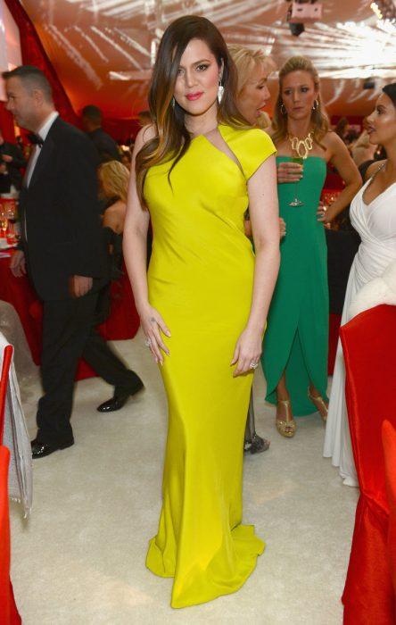 Khloe Kardashian usando un vestido largo de color amarillo
