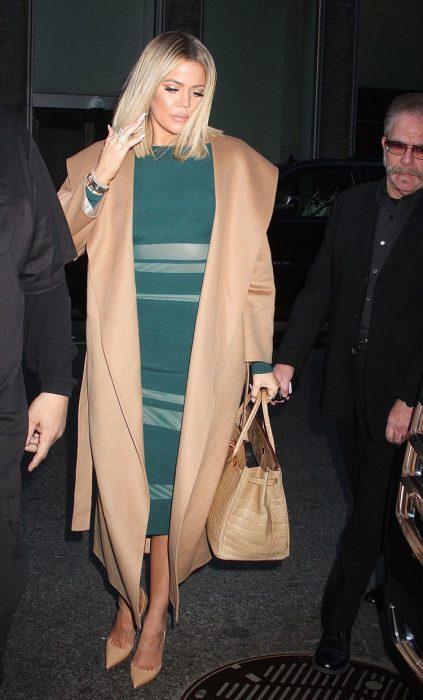 Khloe Kardashian usando un vestido color verde con abrigo beige