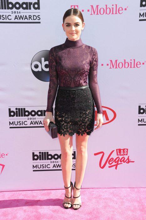 Lucy Hale usando una falda negra con top guinda