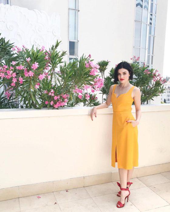 Lucy Hale usando un vestido de color amarillo y zapatos rojos