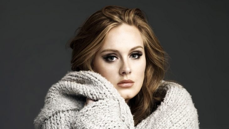 Adele usando suéter gris claro