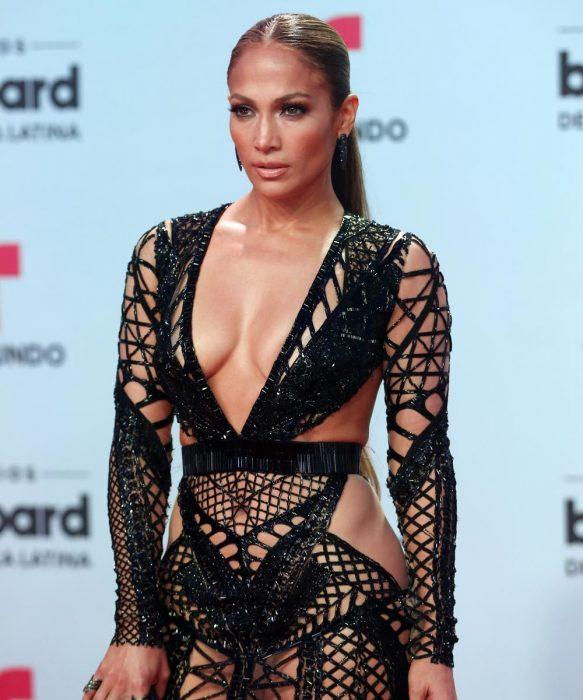 Cantante Jennifer Lopez mirando hacia la cama en una alfombra roja