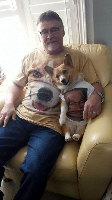 Dueño de un corgi sentado junto a su perro mientras usan playeras con sus rostros