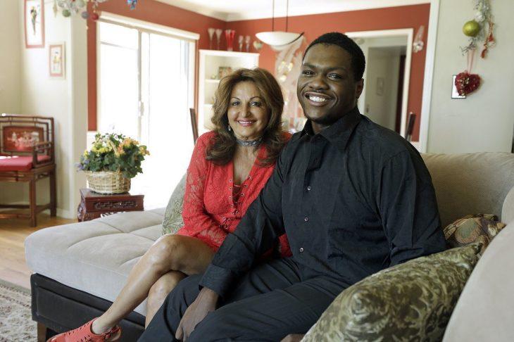 Mujer sentada en el sofá junto a un hombre que rescató cuando era un bebé