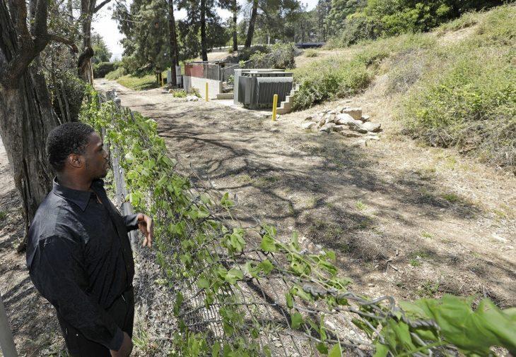 Hombre parado frente a una cerca viendo el lugar donde lo abandonaron de bebé