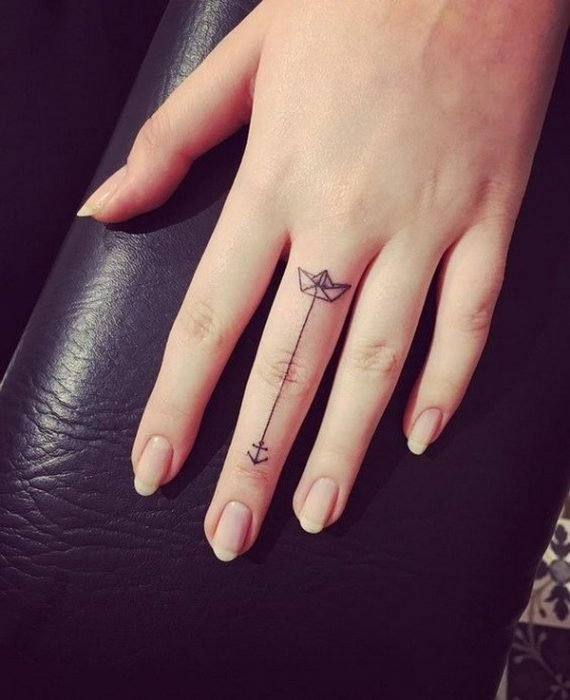 Tattoo of a boat and an anchor on the middle finger