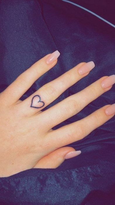 Tattoo of a heart on the middle finger