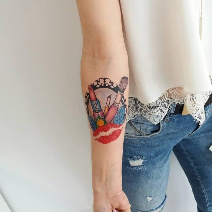 Tatuaje de maquillje con labiales, brochas y un espejo