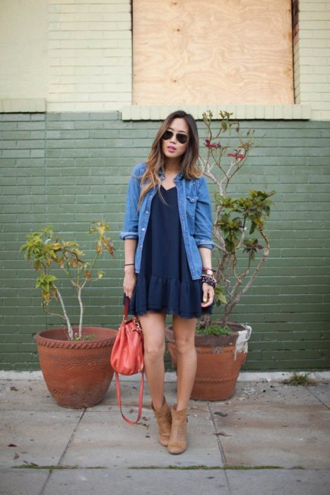 Chica para en la calle usando un vestido azul y bonites café
