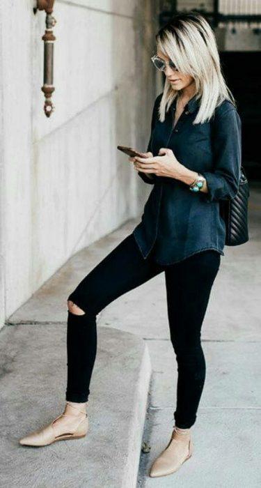 Chica parada en la calle usando unos flats de color dorado