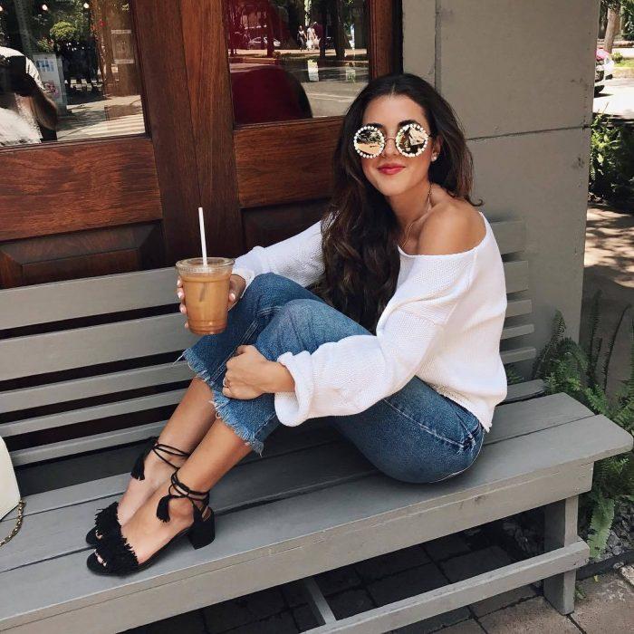 Chica sentada en una banca tomando café y mostrando sus zapatos de tacón