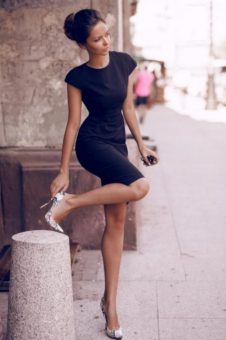 Chica parada en la calle enseñando sus zapatos stilletos