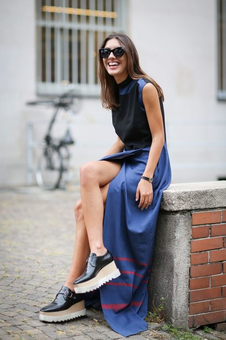 Chica sentada en la calle mostrando sus zapatos de plataforma