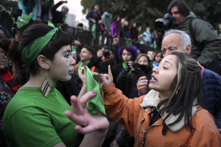 mujer con pañuelo verde y mujer enfrente discutiendo