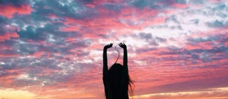 mujer manos arriba cielo rosa