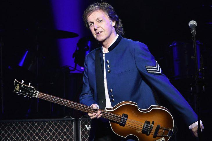 Paul McCarty sosteniendo su guitarra en el escenario