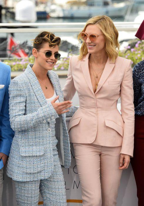 mujer con saco rosa y mujer con traje azul cuelo