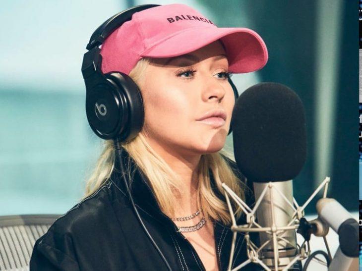 mujer rubia con gorra rosa audifonos y microfono