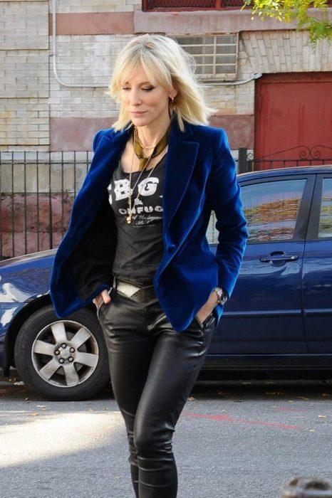 mujer rubia con saco de terciopelo y pantalones de piel