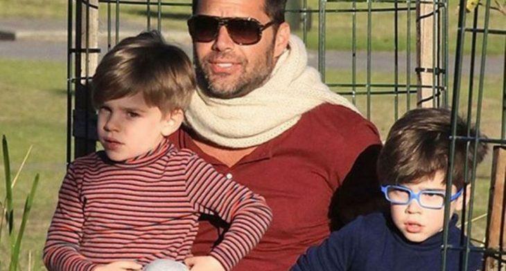 hombre con lentes y bufanda junto a niños