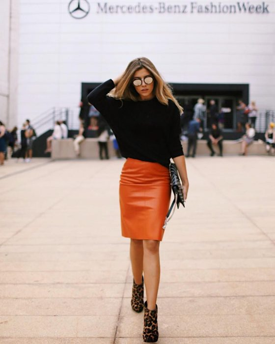 mujer con falda naranja de piel y sueter negro