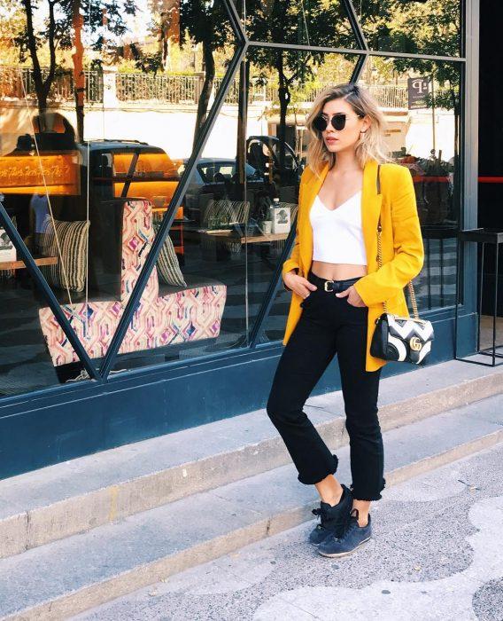 mujer con pantalón negro bralete blanco y saco amarillo