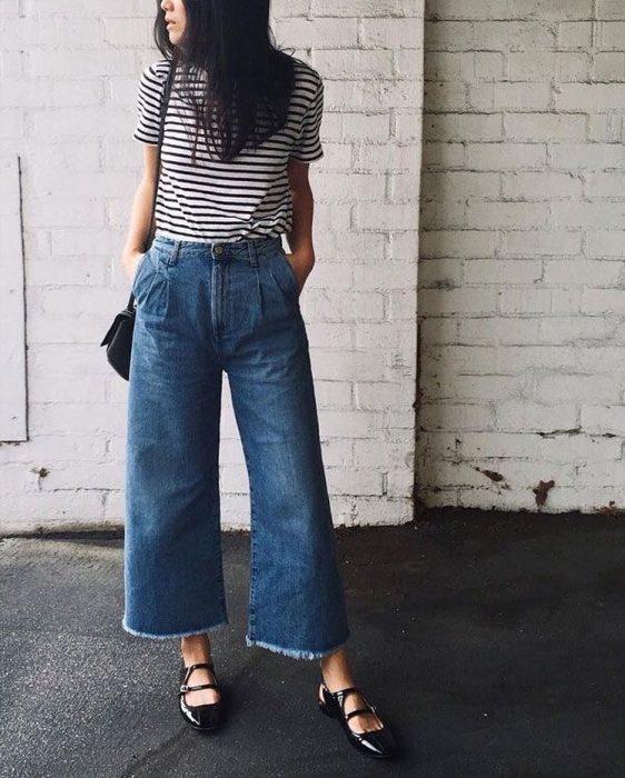 mujer con pantalón de mezclilla y camisa de rayas