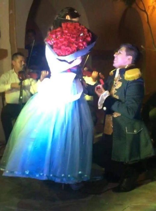 mujer con ramo de rosas y hombre hincado