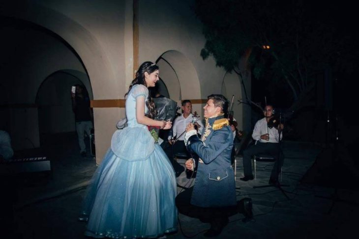 mujer con vestido de princesa y hombre hincado