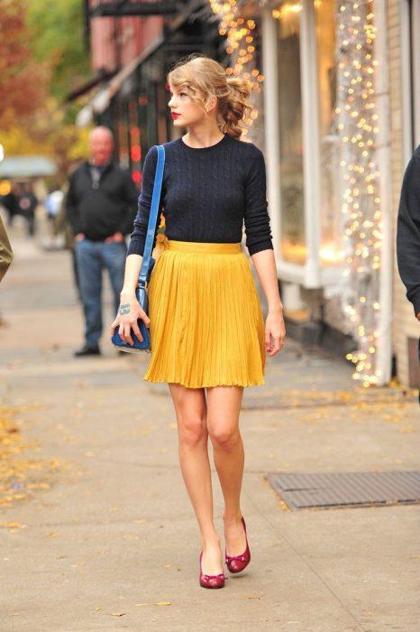 mujer con falda amarilla y zapatos rojos