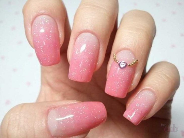 manos de mujer con uñas rosas