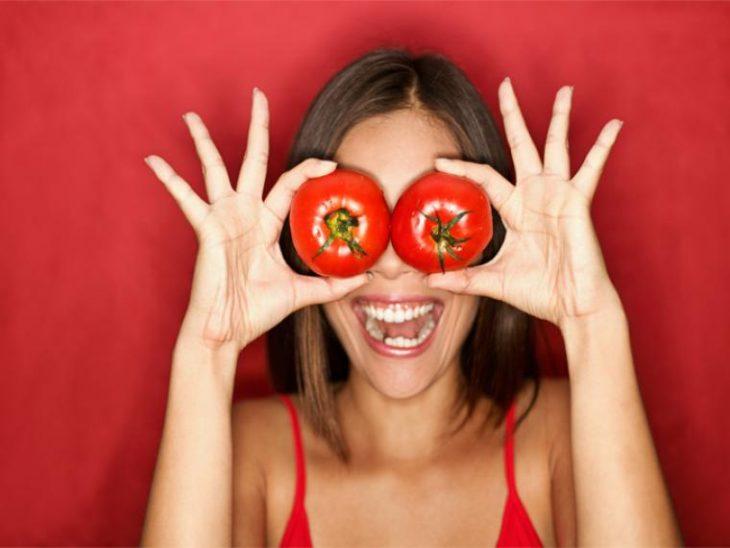 chica jugando con tomates