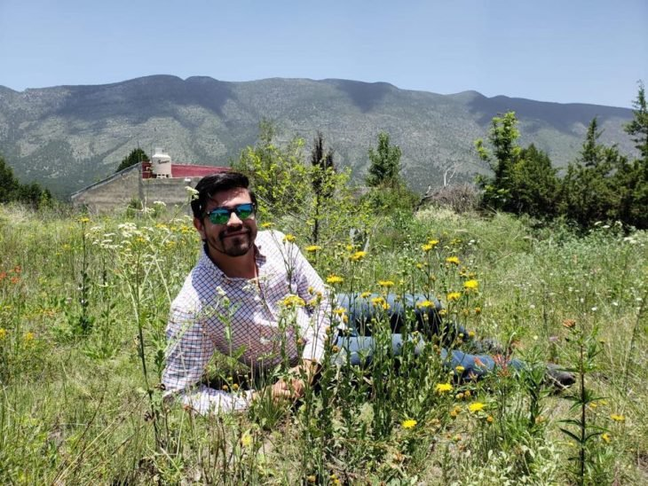 Chico recostado en el pasto posando para una sesión de fotos