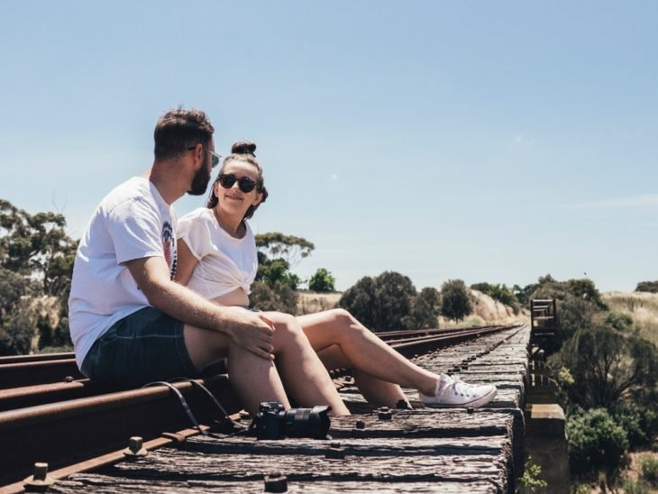 pareja de novios sentados en unas vías