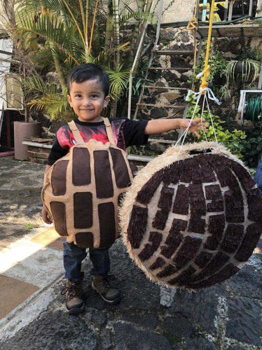Niño vestido de concha con una concha de piñata