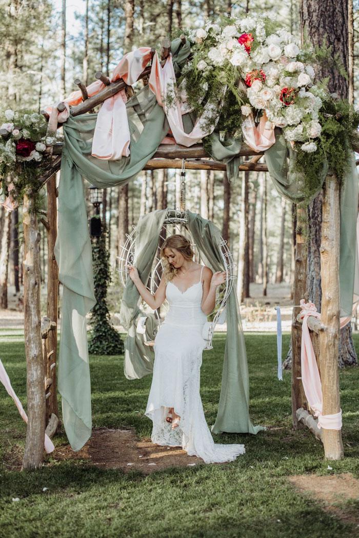 Novia sentada en un columpio durante la sesión de fotos de su boda