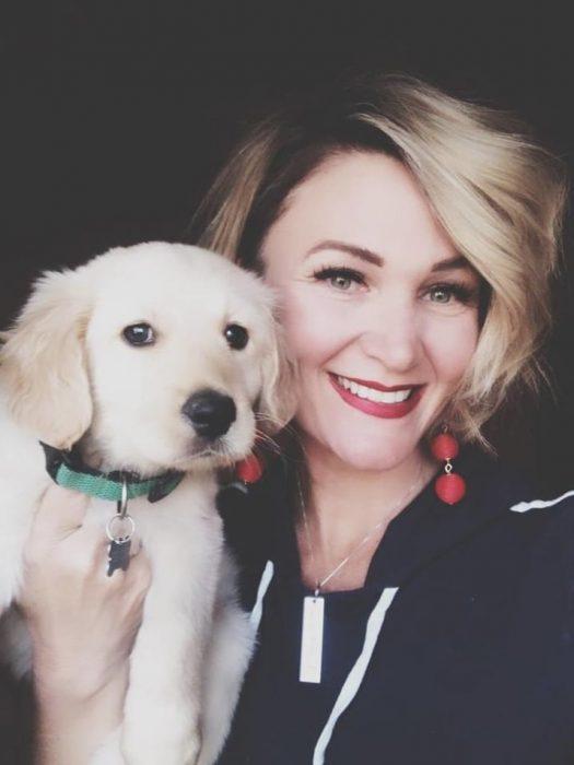 chica cargando a su cachorro