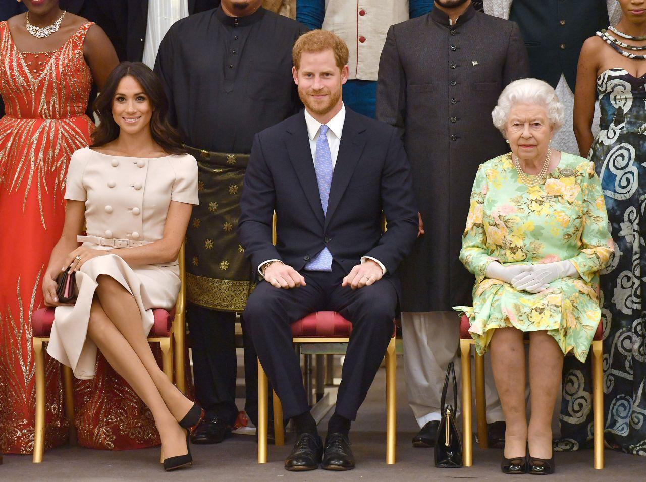 Meghan Markle con las piernas cruzadas frente a la reina