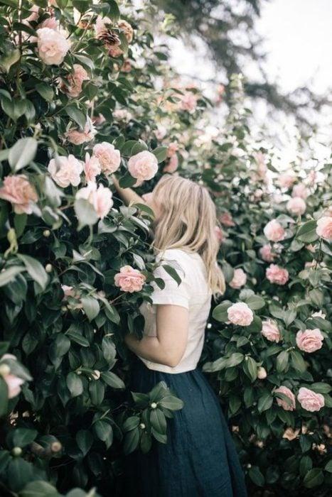 chica oliendo rosas