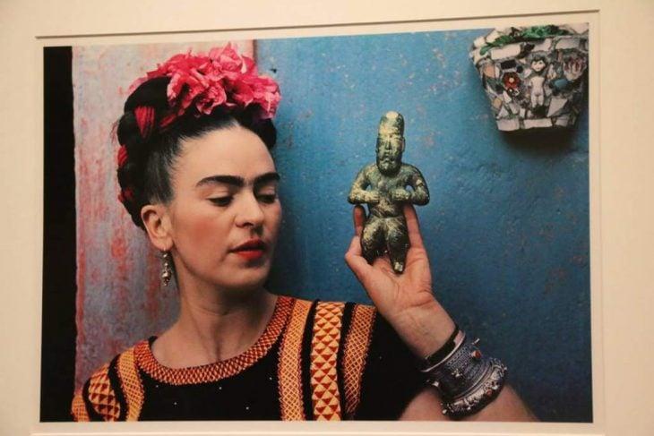 mujer con chongo y flores con figura en su mano