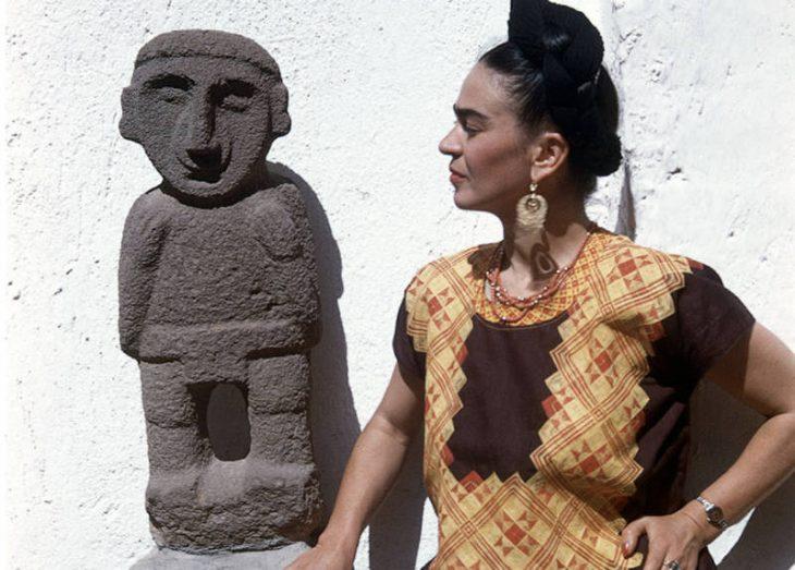 mujer con chongo mirando escultura indigena